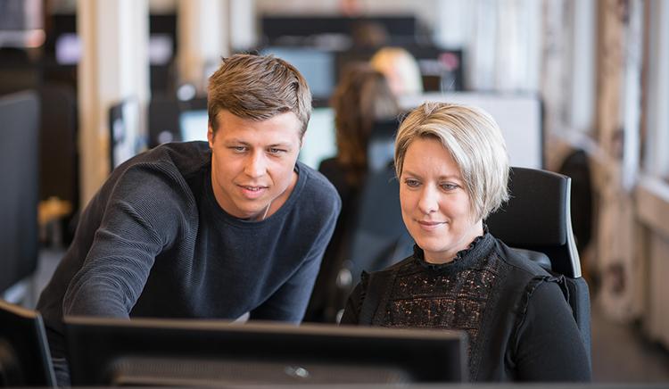 Mann og dame foran dataskjerm - HMS- og kvalitetsrådgiver søkes