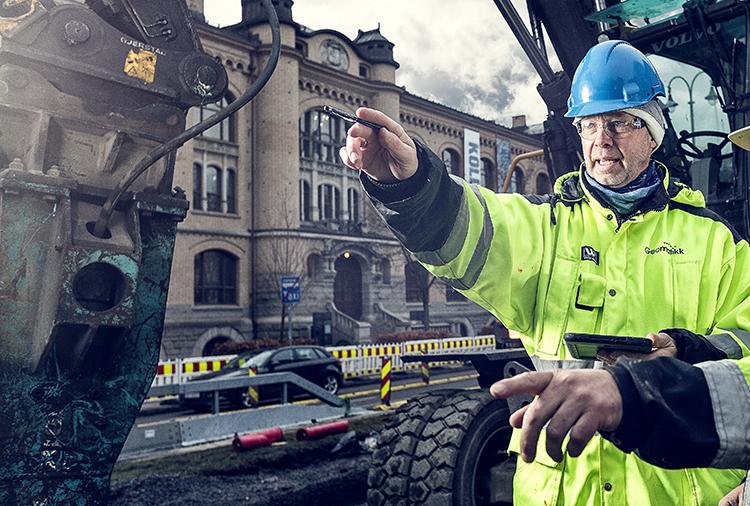 Mann med hjelm som peker på anleggsområde