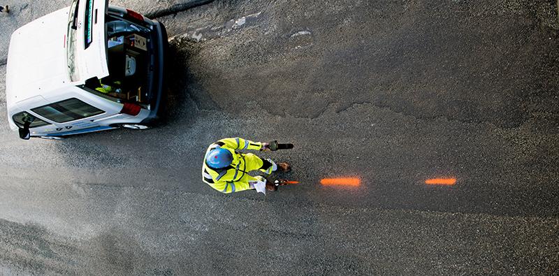Bilde av mann ovenfra som spraymarkerer på asfalt